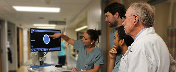 Dr. Gallagher and fellows examining scan during rounds
