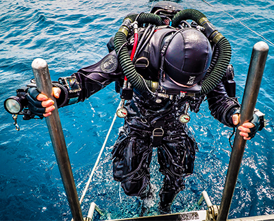 Scuba diver climbing out of the water into a boat